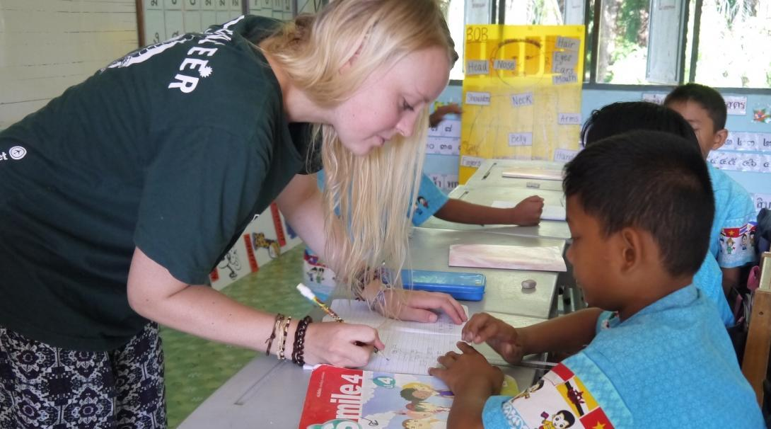 A volunteer corrects the work of her students during her teaching work experience in Thailand.